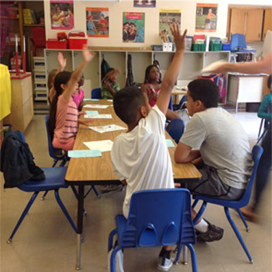 Stonebridge World School Student Raising there hands in class